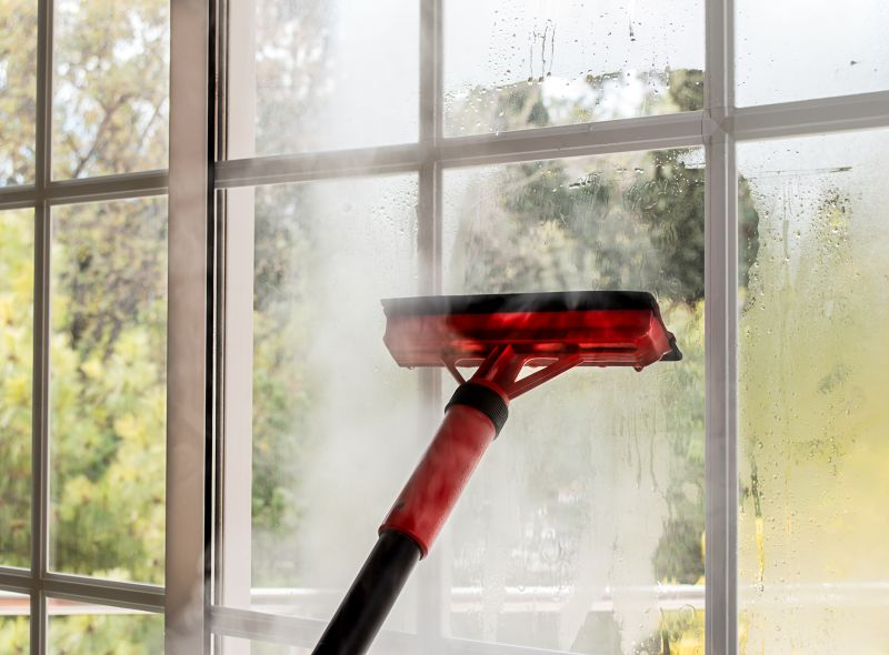 close up of cleaning window glass with steam