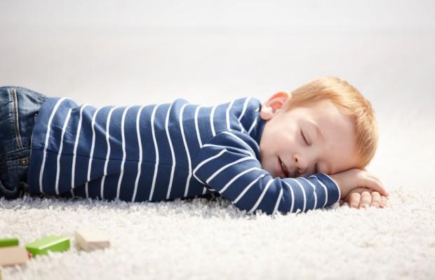 8747094 - cute 3 year old boy falling asleep on floor at home.