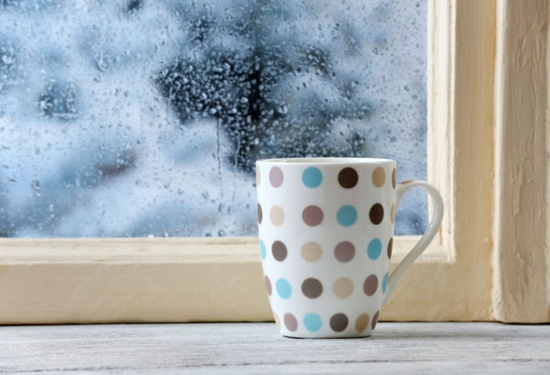 37414417 - cup of hot drink on windowsill on rain background