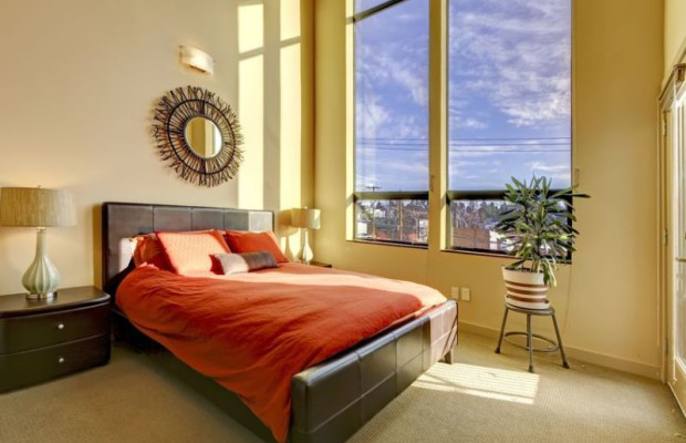 12913821 - large high ceiling bedroom with red bed and yellow walls.