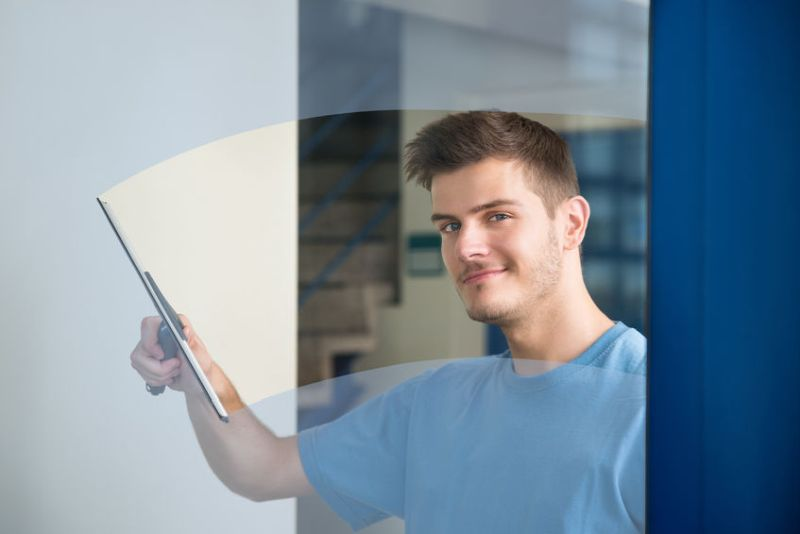 45610024 - young male worker cleaning glass with squeegee
