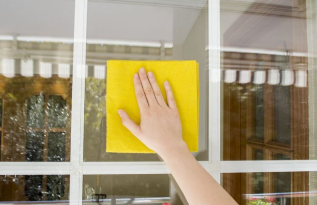 24365034 - woman cleaning glass outdoor with a yellow cloth
