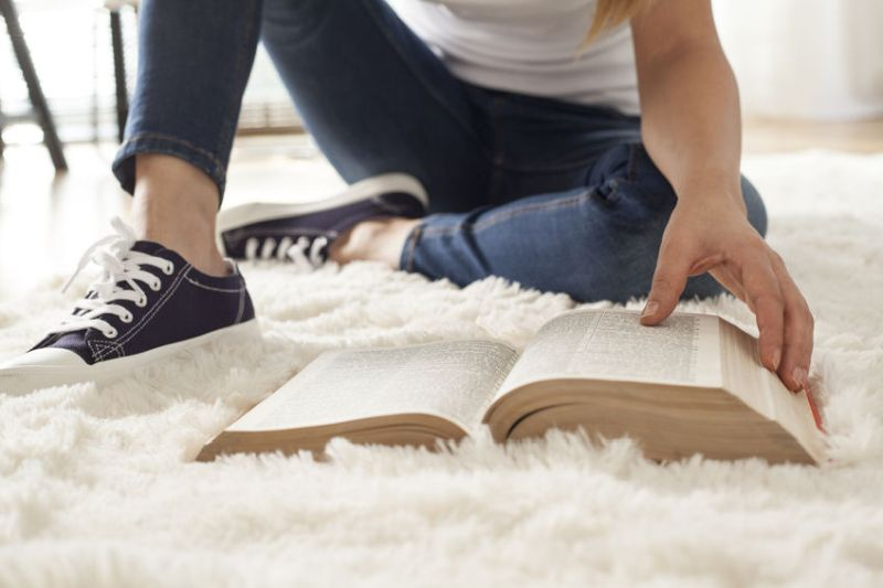 64792038 - young woman reading book on carpet