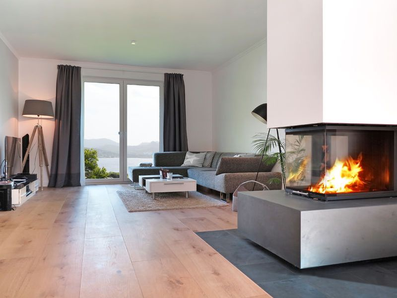 45064767 - modern living room with fireplace and a view to the coast