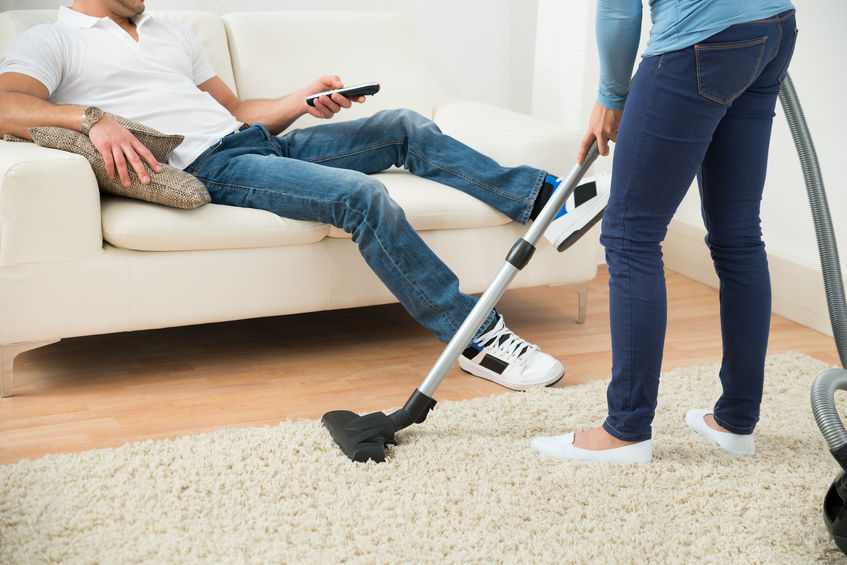 41317965 - close-up of a woman cleaning carpet in front of man sitting on couch